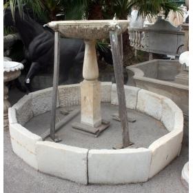 Fuente antigua con cerco de estilo andaluz con cabezas y salidas de agua de bronce