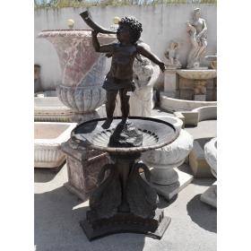 Fuente de bronce de un plato con figuras de cisnes en la base y angelito con instrumento