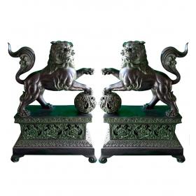 Pareja de leones chinos posados con bola y sobre peana realizado en bronce