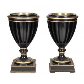 Pareja de jardineras en forma de copa de madera lacada en negro y dorado de gusto neoclásico. Recipiente interior de metal.