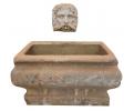 Fuente de pared antigua realizada en piedra con mascarón