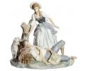 Escultura de porcelana Lladró que representa a una mujer inclinada sobre un hombre dormido con perro.